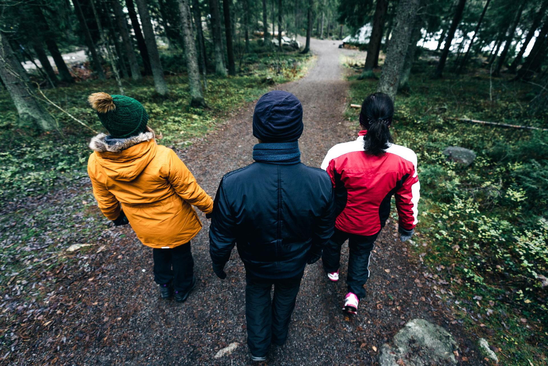 Kolme ihmistä kävelee polkua pitkin samaan suuntaan.