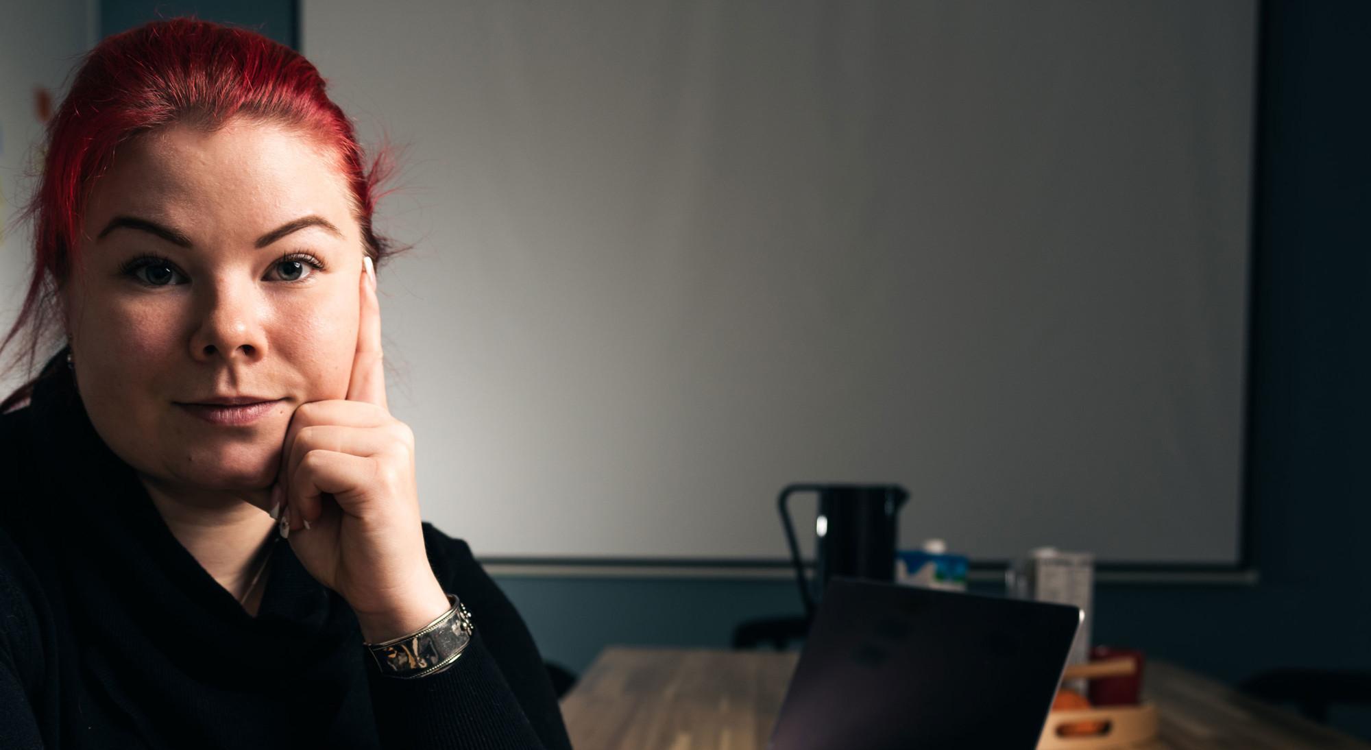 Nainen istuu taukotilassa läppärin edessä.