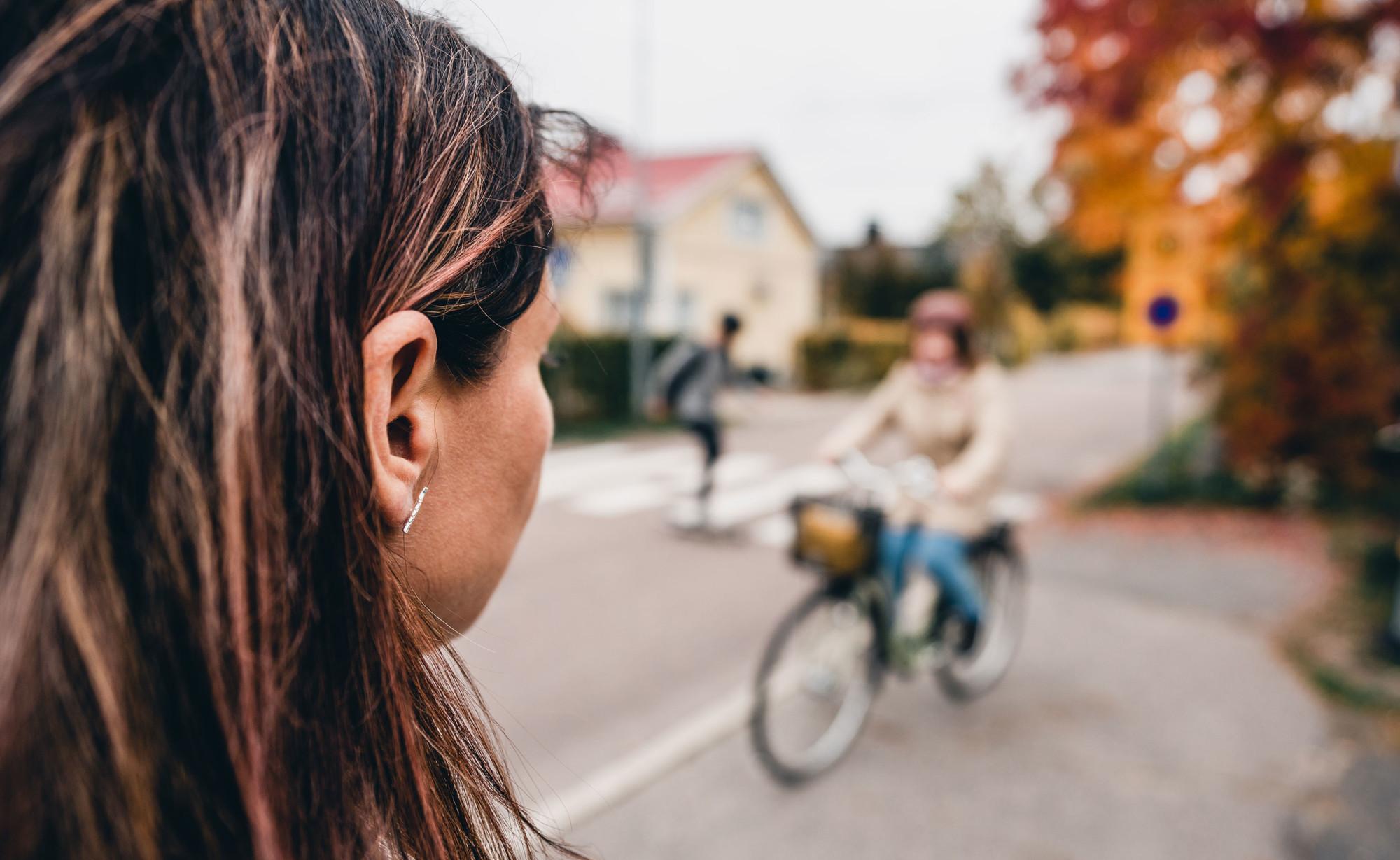 Ihmisiä pyöräilee, kävelee ja skeittaa kadulla.