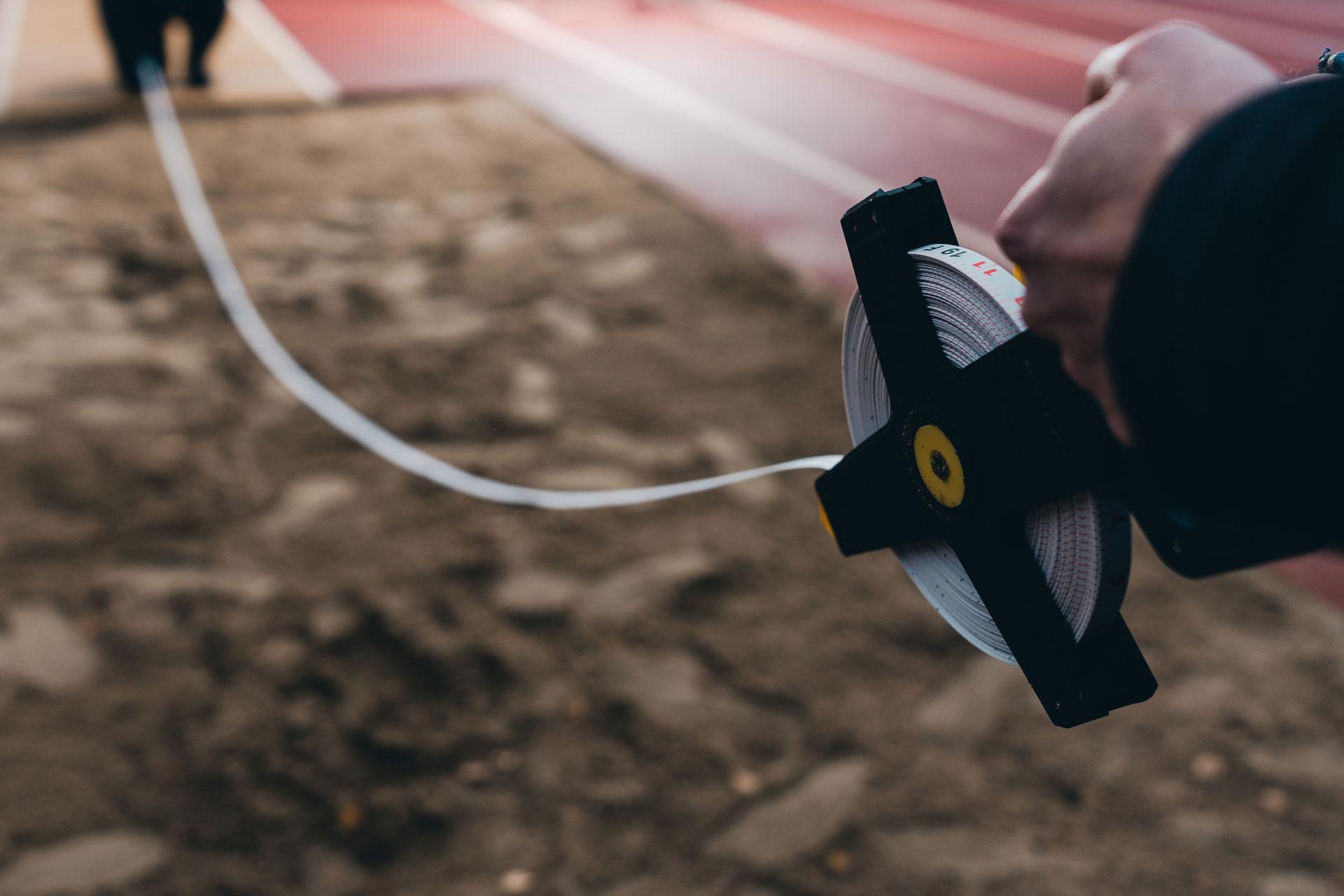 Pukumiehet mittaavat pituushyppytulosta.