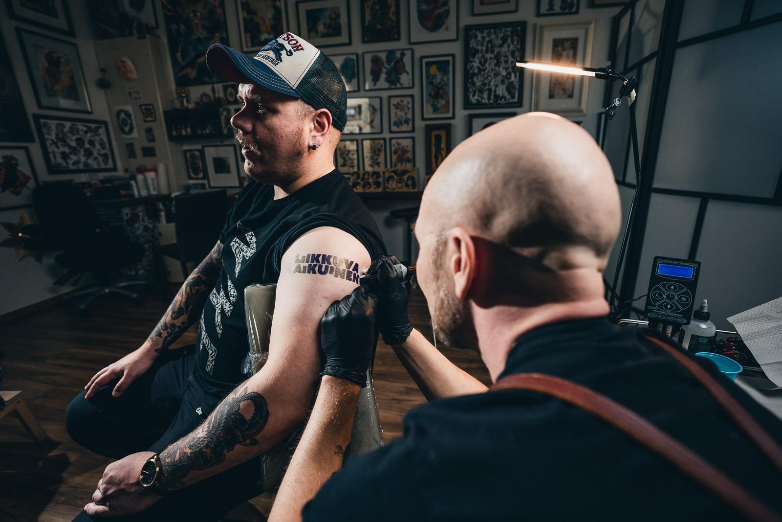 Tatuoija tatuoi miehen olkapäähän Liikkuva aikuinen -logoa.