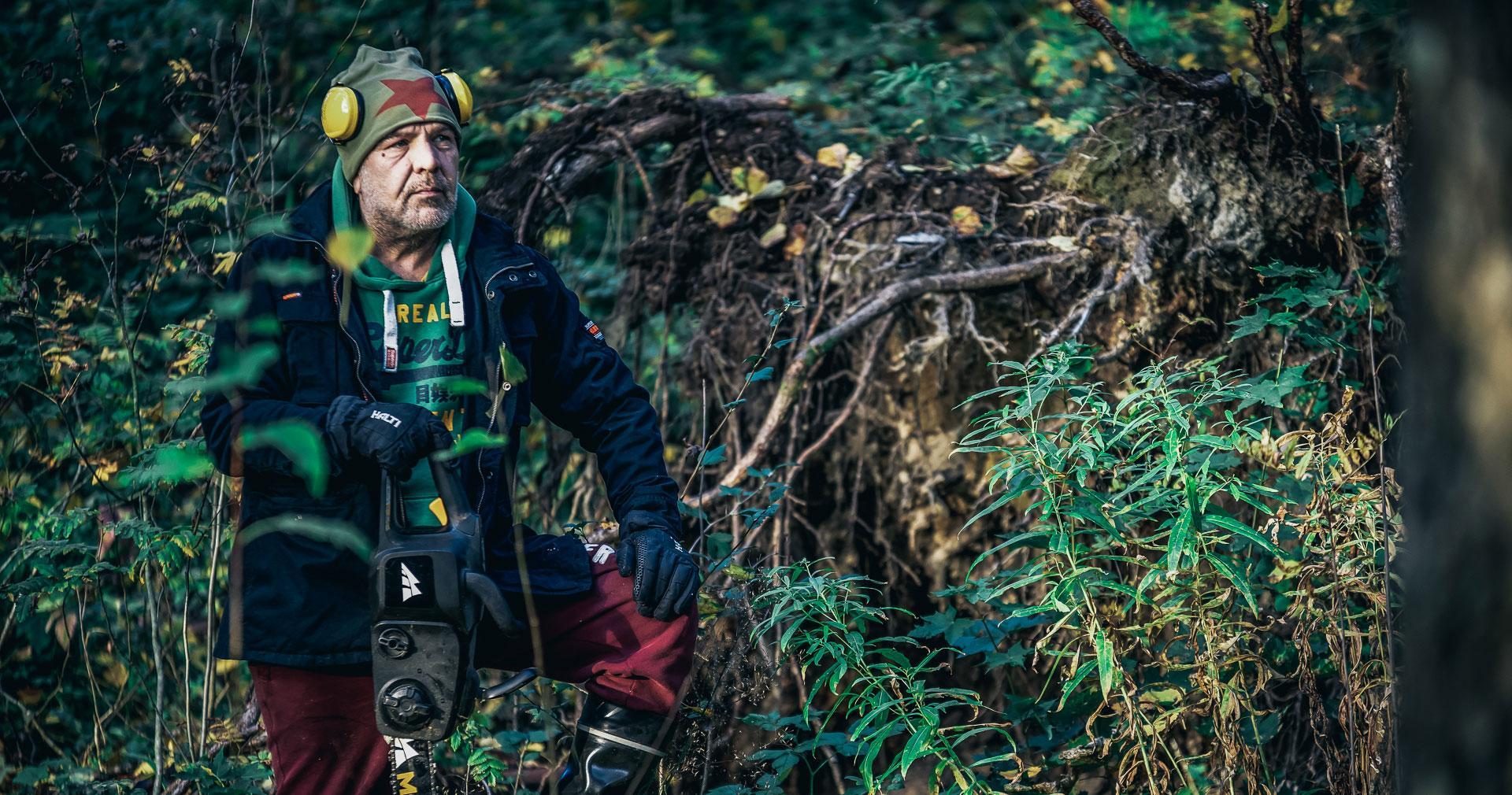 Mies seisoo metsässä moottorisaha kädessä.