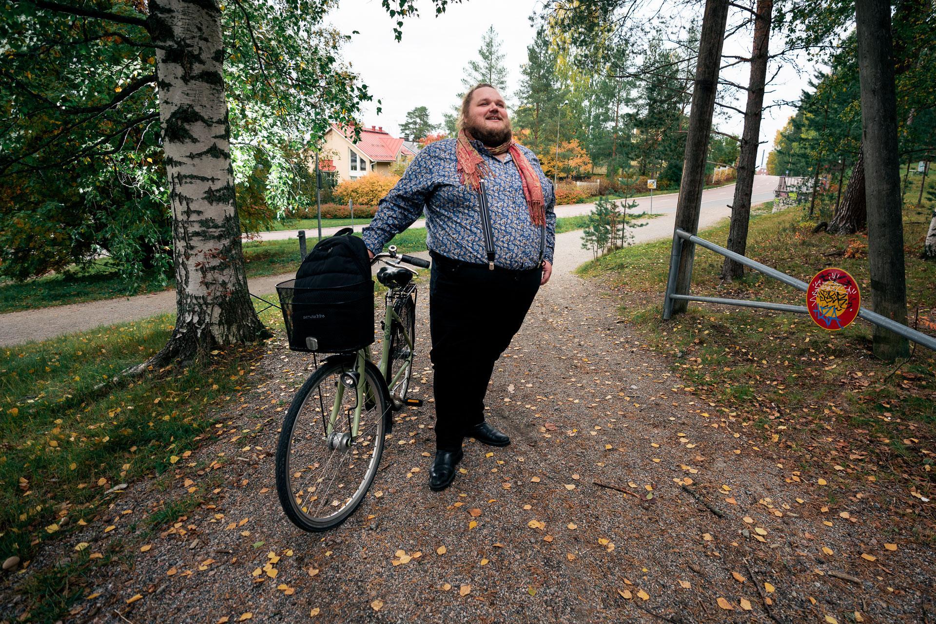 Mies seisoo pyöränsä vieressä.