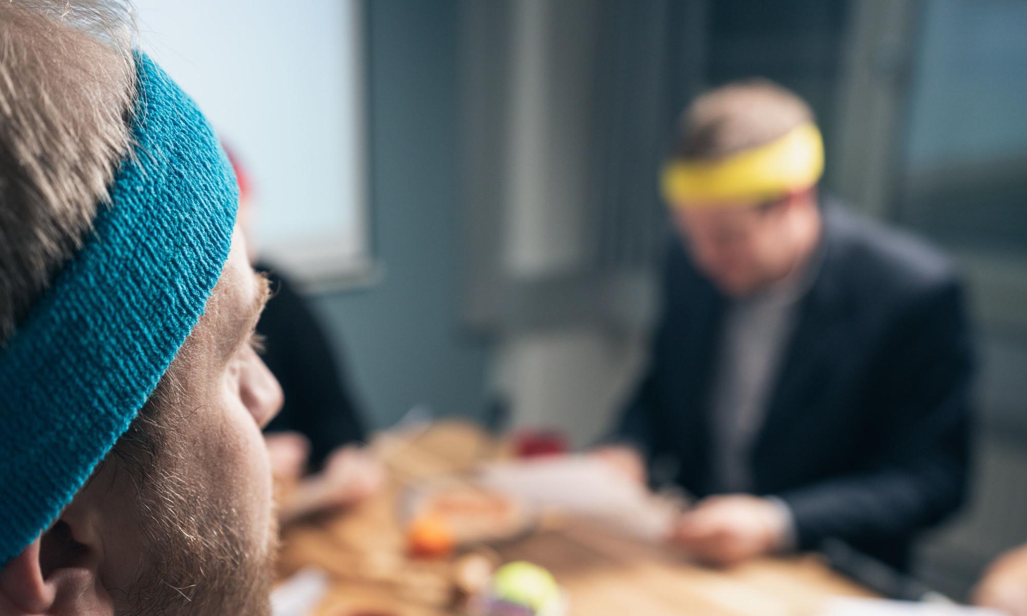Liikunnan edistäjät istuvat toimistossa hikunauhat päässä.