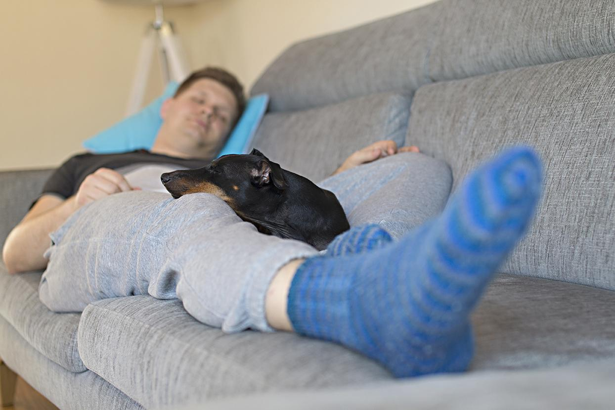 Mies nukkuu sohvalla.