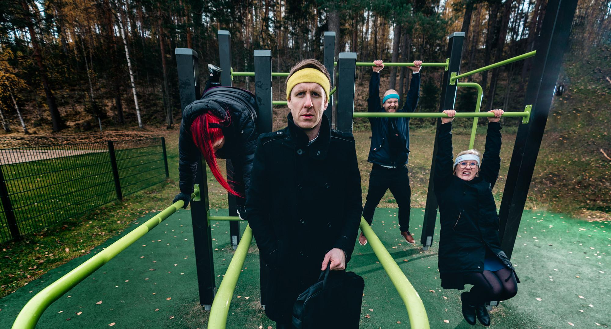 Päättäjät kokeilevat ulkoliikuntapuiston telineitä.