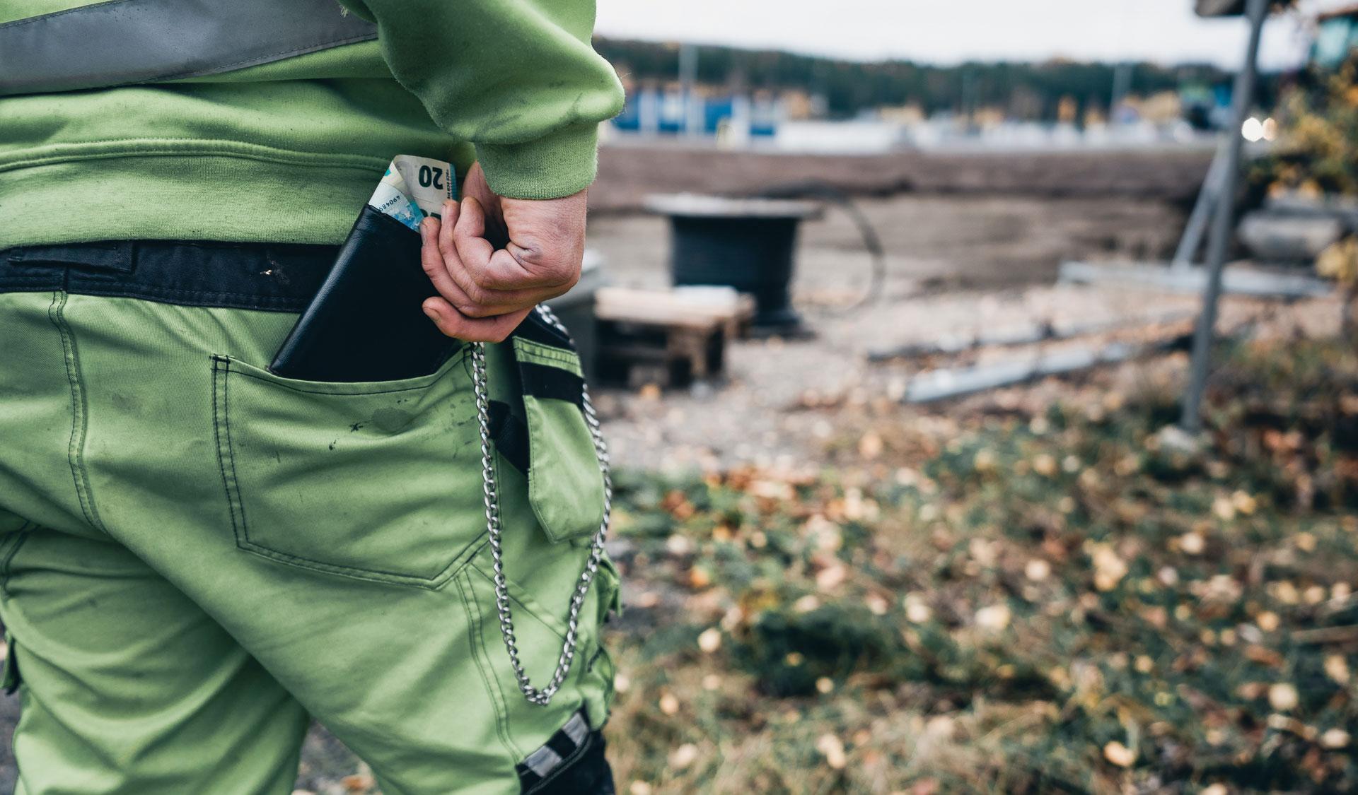 Rakennusmies kaivaa lompakkoa takataskustaan.