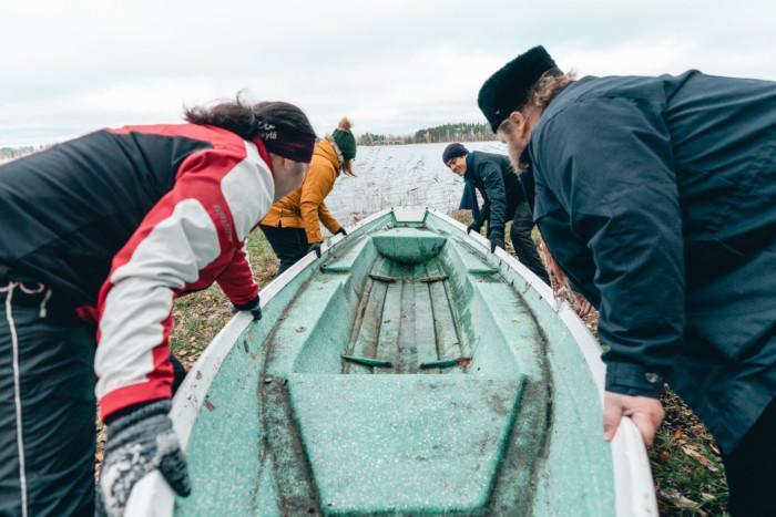 Kaksi naista ja kaksi miestä työntävät venettä vesille.