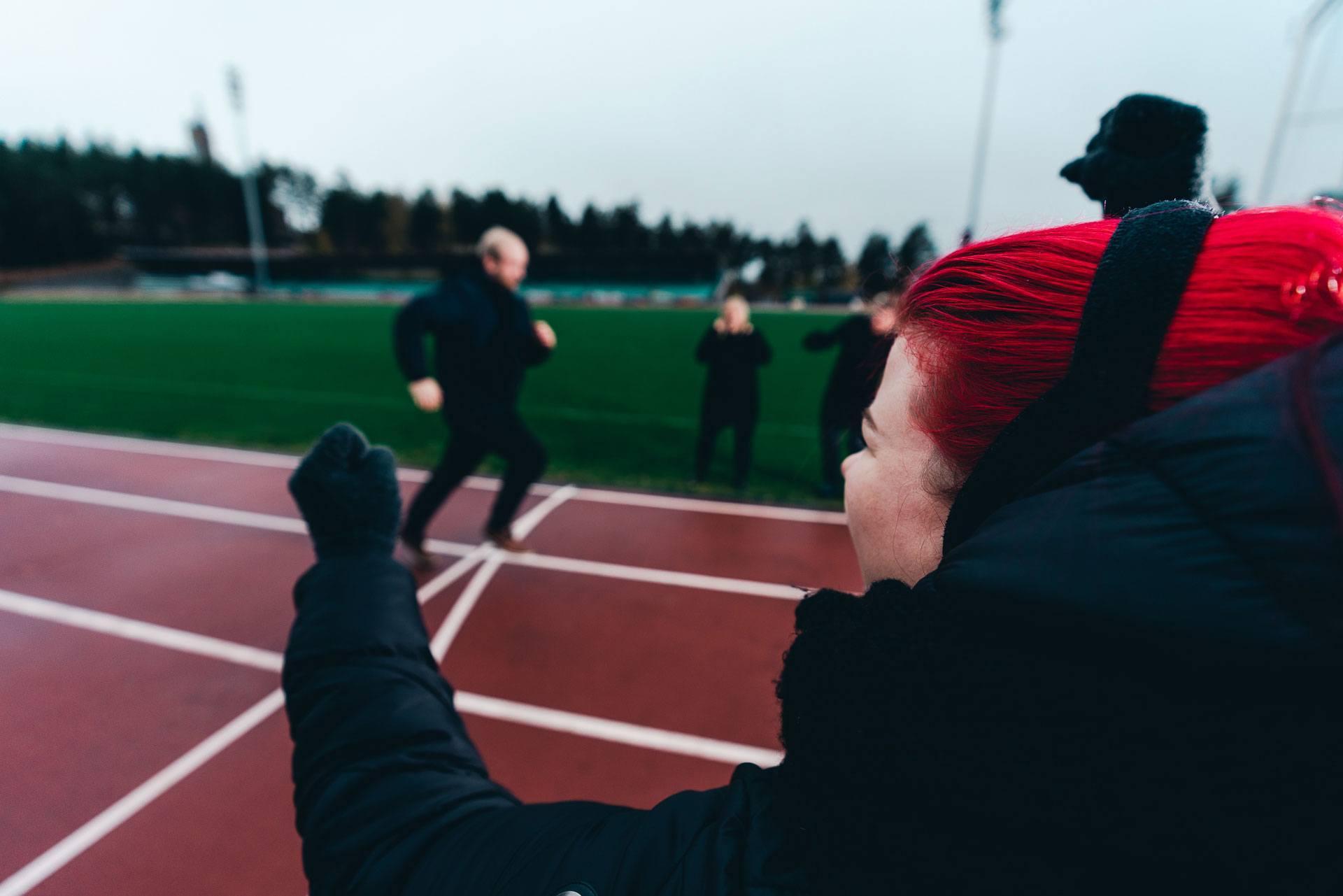 Mies juoksee urheilukentällä maaliin ja nainen tuulettaa.